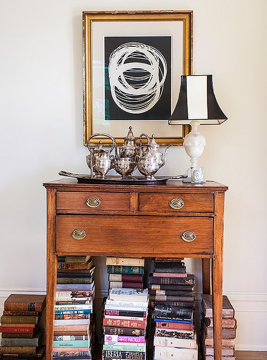 An Early American huntboard offers a simple handsomeness plus storage space for cards and poker chips. A traditionalist might have filled the space beneath it with an urn; Sara chose books.