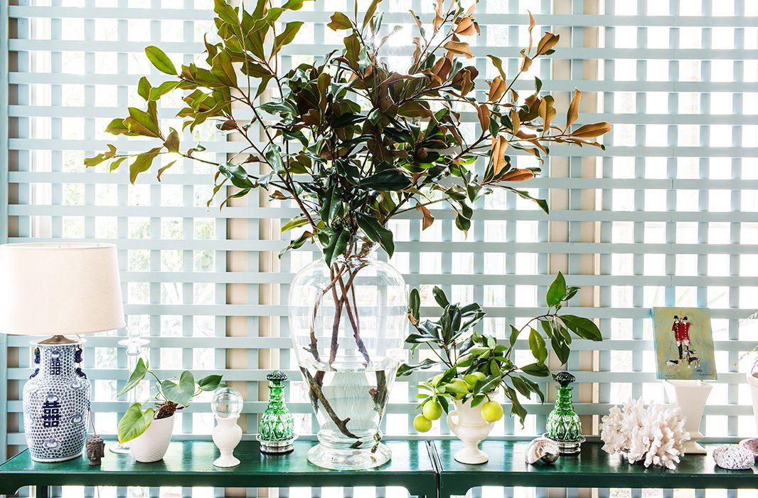 Hand-me-down console tables are topped by more hand-me-downs, accented by bouquets of magnolia branches and Meyer lemons clipped from trees in the backyard.