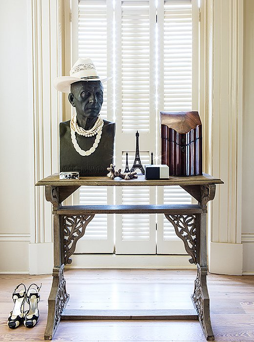 "In a bedroom antechamber, a table by Thomas O'Brien displays a vintage knife holder (now used to store letters) and, adding a little levity, a vintage bust decked out in a hat and pearls. ""I just have a thing for busts. When you're lonely it's like having some friends in the house."""