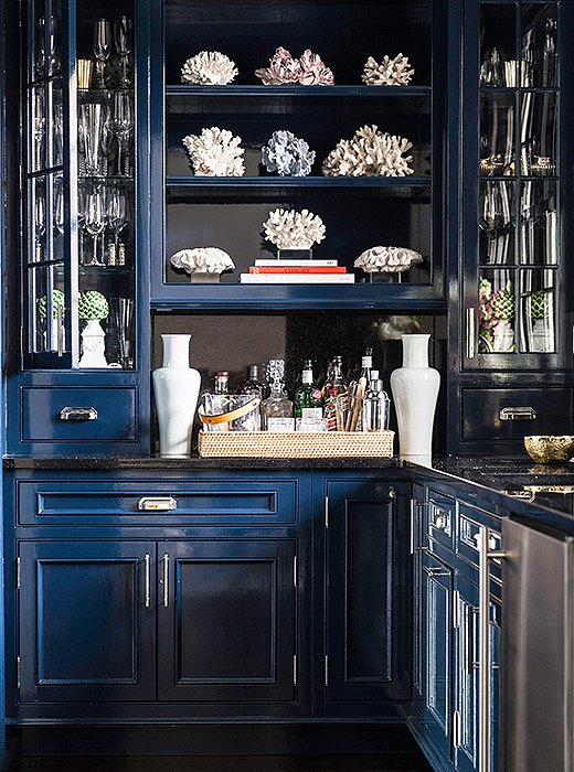 "Sometimes a coat of paint is the best zhushing move. When the family first moved in, the bar was ""old school and very masculine,"" Sue says. But now that it's been painted a deep glossy blue, a shade inspired by Pinterest hunts, the space feels sexier and more modern."