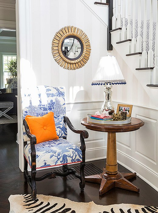 A toile-upholstered chair feels fresh when paired with a zebra rug.