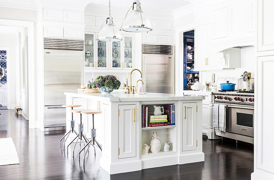 "Sue embraces mixed metallics in the kitchen via the silver-trimmed ceiling pendants, saved from the family's former house (""Those were the first expensive things I ever bought,"" she says) and brass faucets and hardware."