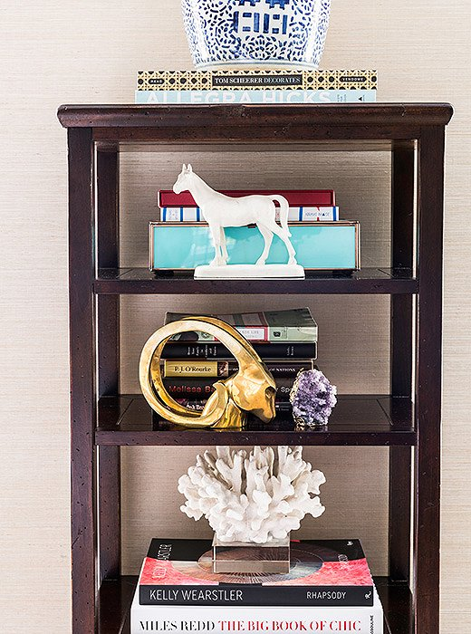 In an étagère, the striking objets—a brass ram's head, a heroic white horse, a bold white coral—more than hold their own among the books.