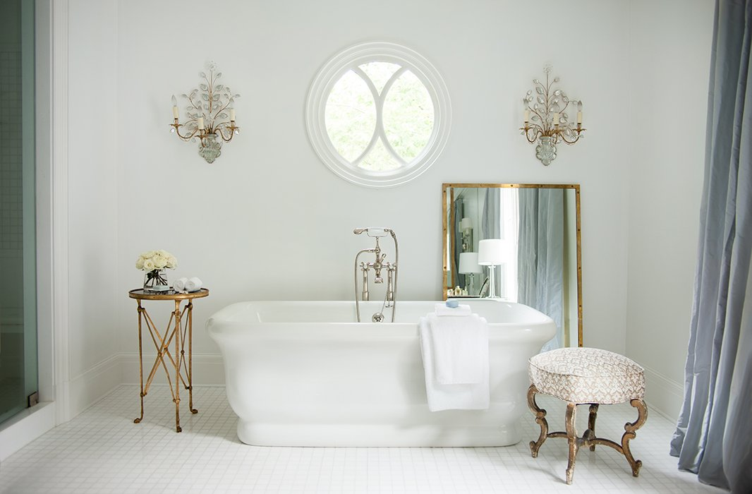 Designer Suzanne Kasler chose curtains in a soft gray-blue silk for her dreamy master bathroom. The cool tone sets off the warm antique-brass finishes and adds to the restful atmosphere. Photo by Erica George-Dines.