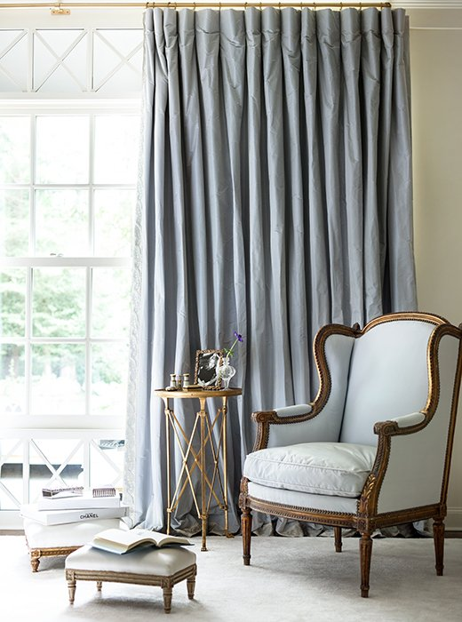 Classic Home Decor With Traditional & French Style. Silk curtains and an upholstered bergère create a restful corner in shades of pale blue. #Frenchstyle #bluebedroom #wingchair #timelessdecor