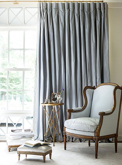 Silk curtains and an upholstered bergère create a restful corner in shades of pale blue.