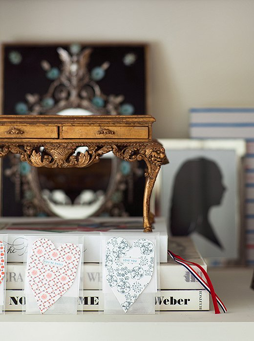 A miniature gilded desk, part of a larger collection of model furnishings, sits atop a stack of books in the bedroom. The silhouette was made in Paris and depicts Suzanne's daughter, who gave her the two heart-shape cards.