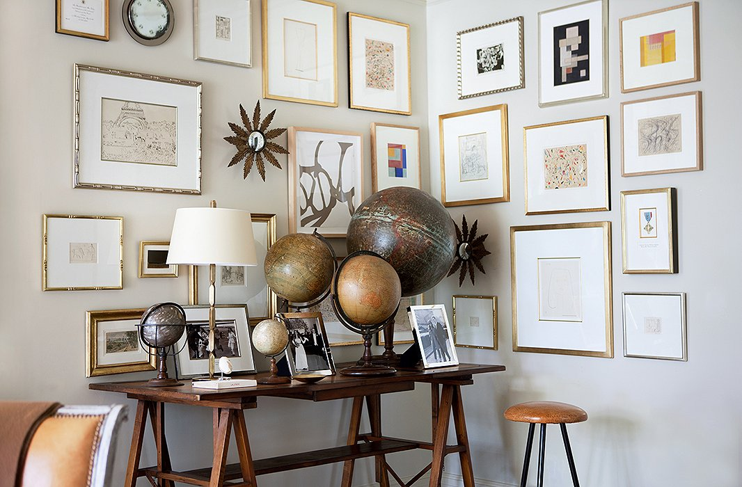 "An ever-expanding gallery wall fills a corner above Suzanne's collection of vintage globes. ""I hang the frames in a random pattern because I'm always adding to it! A constant theme has been collecting art and then finding enough walls to hang it on."""
