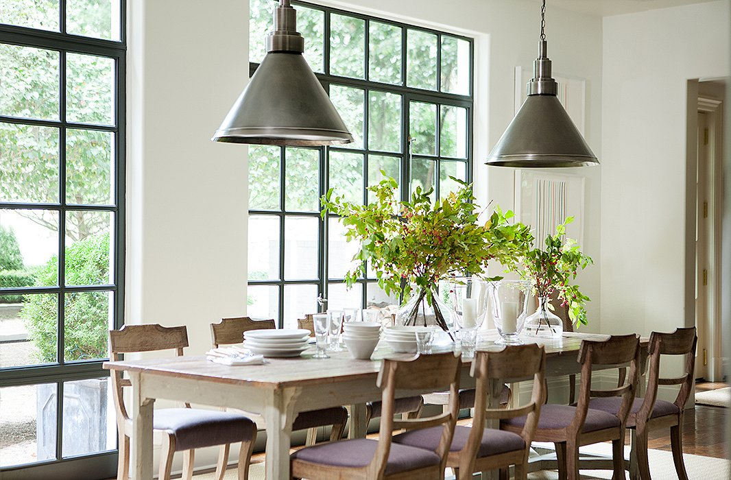 Sunlight pours into the breakfast area through steel casement windows; their industrial feel is carried through to the pewter pendant lights.