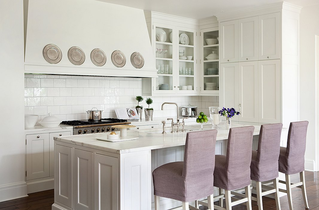 Crisp and clean in bright white, the kitchen is the hub of the home. Slipcovered barstools designed by Suzanne add softness to the marble-top island.