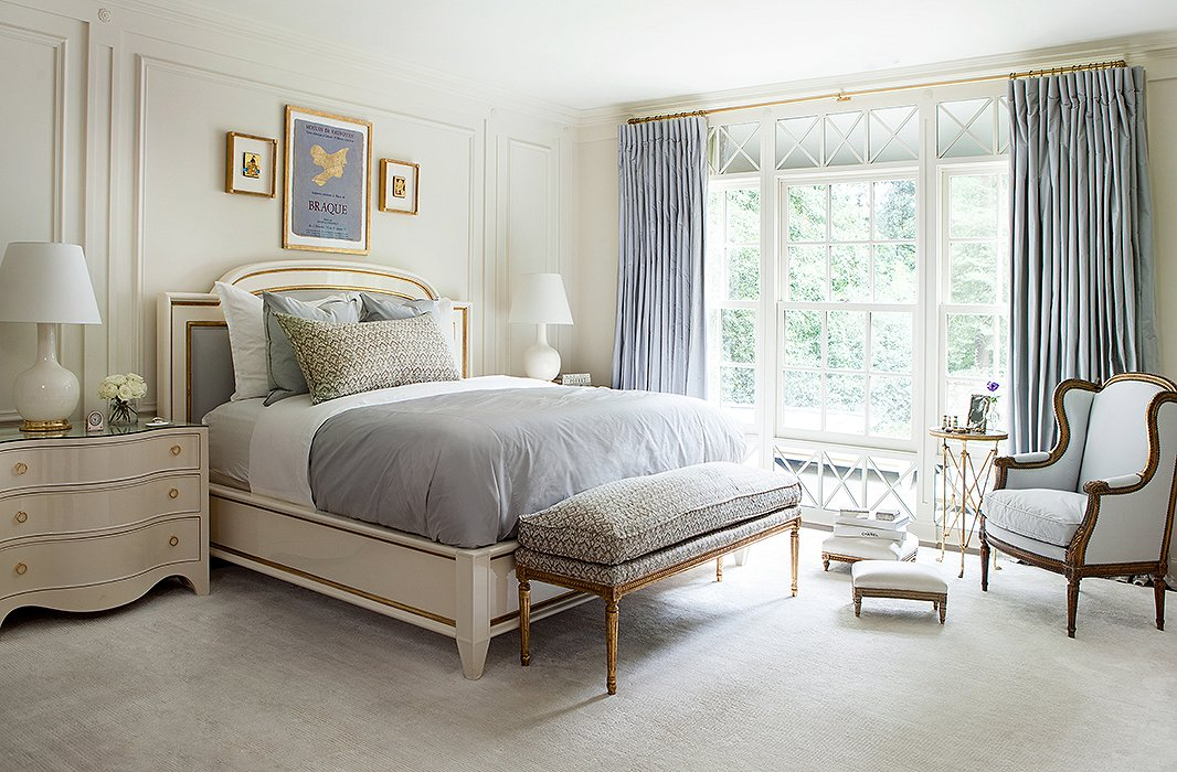 Touches of gold are woven throughout Suzanne's bedroom, from the detail on the bed to the base of the table lamp to the ornateframe of the upholstered bench.