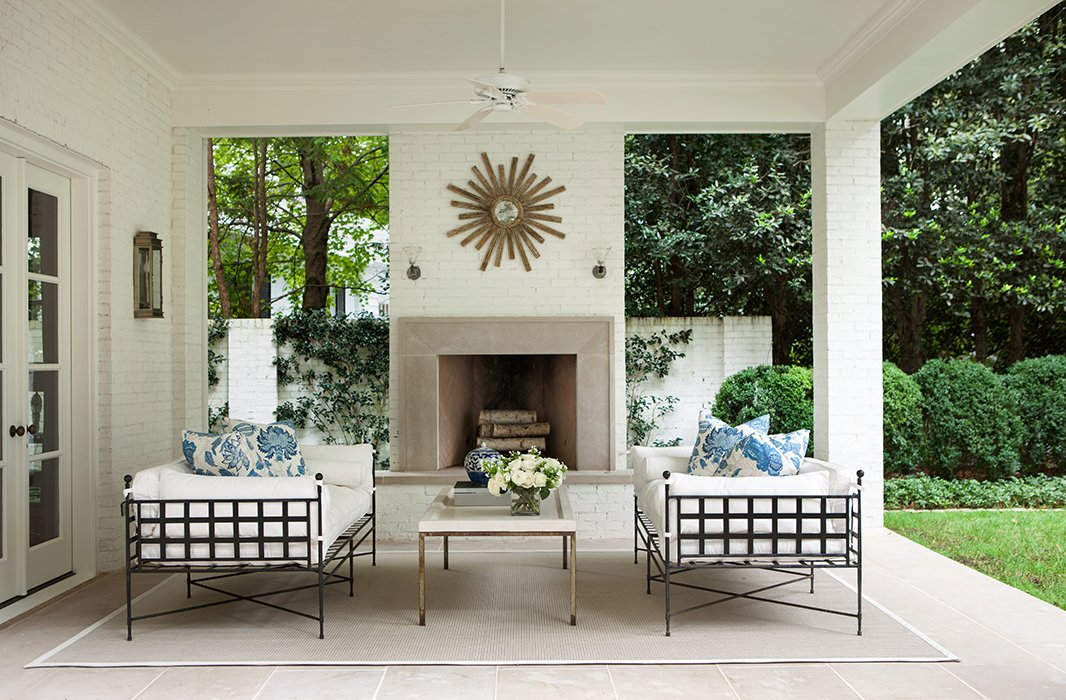 """I love having a house that interacts with the outdoors,"" Suzanne says. On the terrace, the furniture's strong lines play nicely off the sunburst mirror and round boxwood hedges."