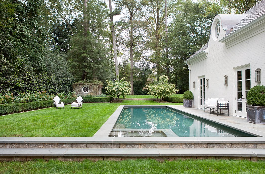 Iron furnishings, antique planters, and a manicured lawnlend this pool a decidedly Parisian feel. Photo by Erica George-Dines.