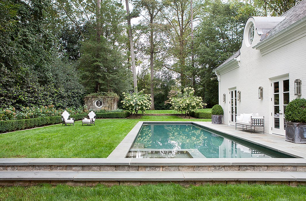 Iron furnishings, antique planters, and a manicured lawn lend this pool a decidedly Parisian feel. Photo by Erica George-Dines.