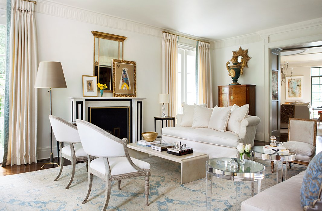 Throughout the home, a restrained palette unifies a mix of styles and eras. Lucite tables, antique Swedish chairs, and a French Moderne-style coffee table form an asymmetrical yet balanced arrangement in the living room.