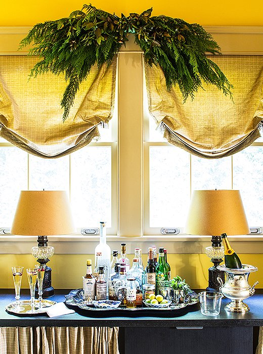 This elegant bar is given just enough holiday flair courtesy of the greenery-dressed curtain.