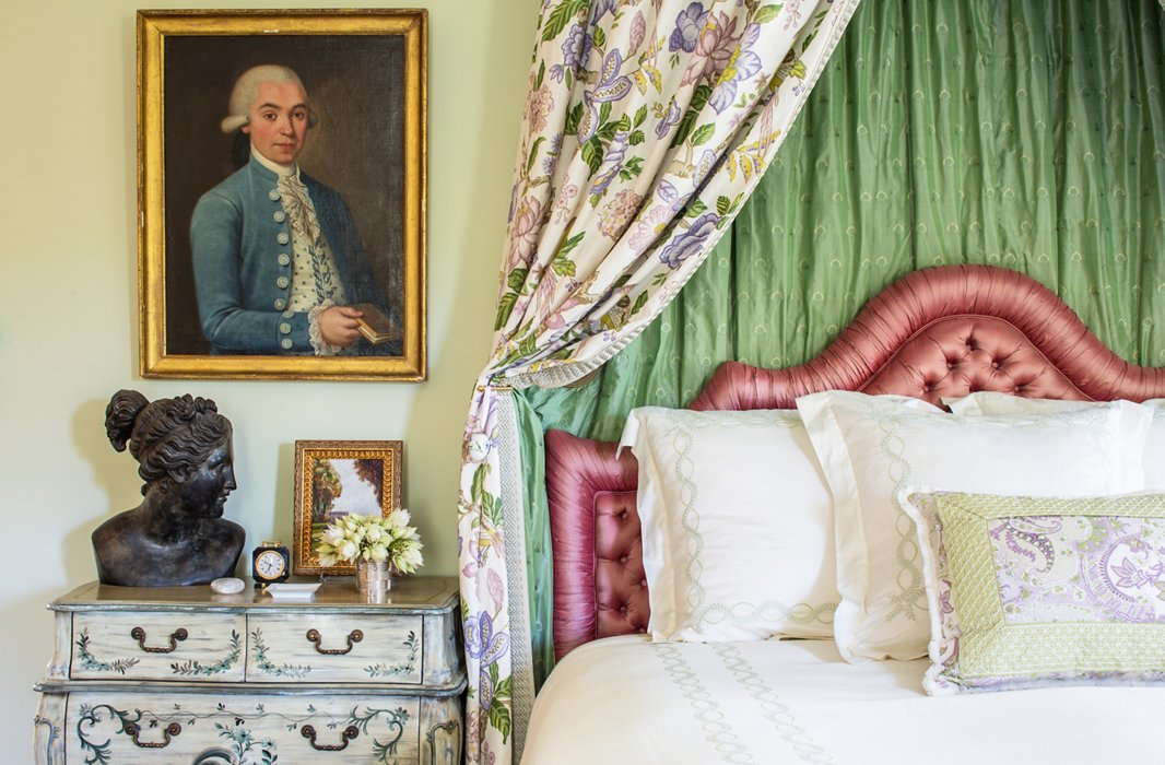 "In Kathleen's room everything is very muted except for the bed, which features a pink satin headboard and drapes made of Timothy's lavender-and-green floral lined in silk. ""I wanted to create a wonderful feminine room using lavenders and greens and pinks."""