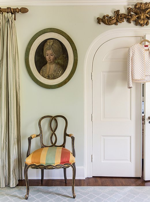 "An oversize stripe modernizes an 18th-century chair and really stands out in the otherwise pale bedroom. ""I like to go with quieter palettes and then let punches of color come in through a pillow, a painting, or an object, but not be overwhelming."""