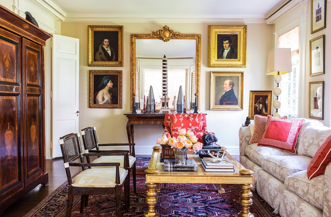 Many of Timothy's fabrics (including those on the red chair, the pillows, the lampshade, and the drapes) are on display in the family room, where Timothy and his partner, Kathleen Scheinfeld, watch TV (hidden from view in the cabinet).