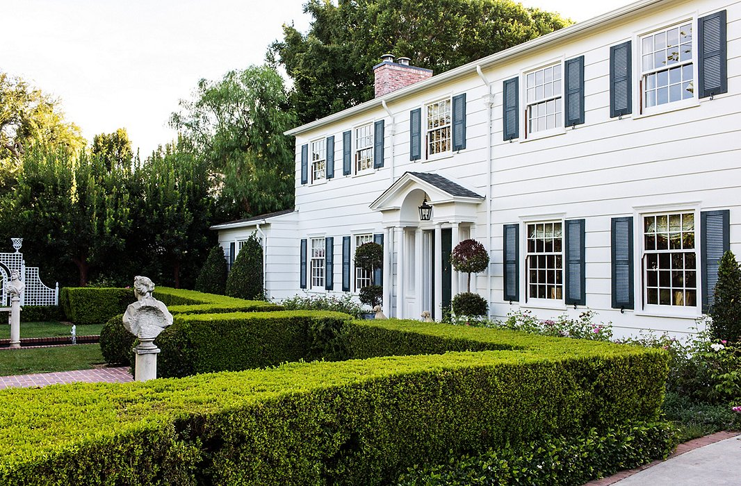 A pair of classical busts, supported by pedestals, add architectural charm to a well-manicured front lawn. Photo by Nicole LaMotte.