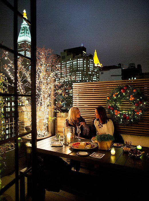Guests cozy up with throw blankets as they chat on the terrace amid stunning views of the Manhattan skyline.