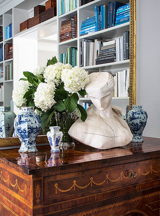 A substantial bust offsets ornate chinoiserie vases and intricate marquetry motifs for a balanced effect.