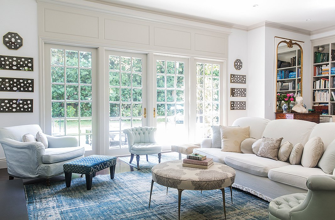 The living space in Windsor's home is anchored in a blue-and-white palette that feels light and modern, thanks to a faded overdyed rug and crisp upholstery. Pale sage chairs add to the soothing ambience.