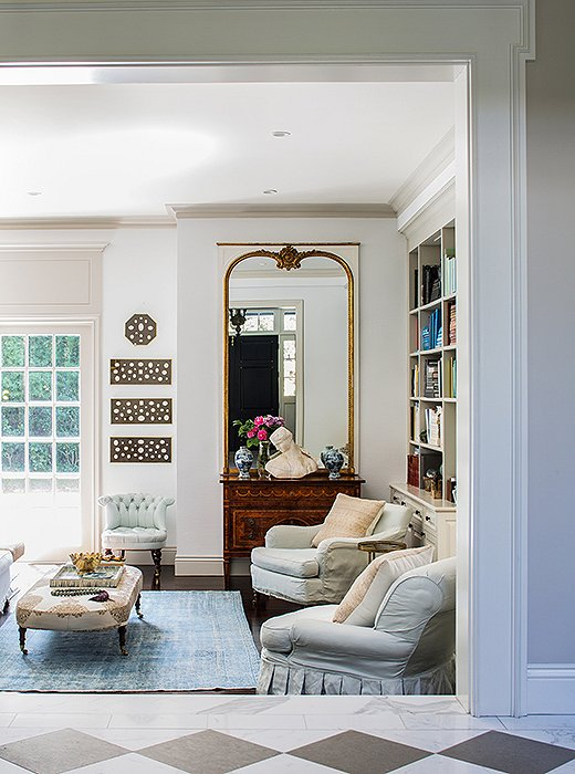 Snowy white walls provide the perfect blank canvas for a formal vignette topped with a classical bust and a mirror as well as for monochromatic art panels and colorful books.