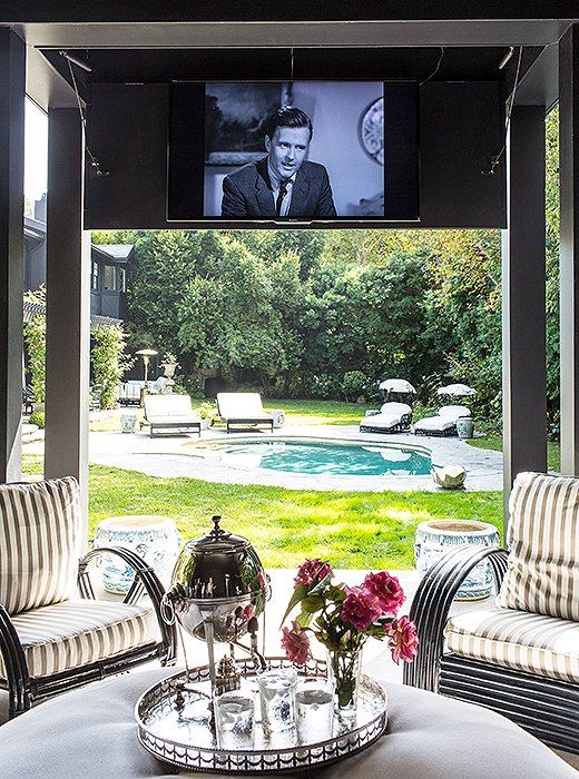 Indoor luxuries big and small—a drop-down movie screen, a silver tray topped with fresh-cut blooms—make the pool pavilion especially comfortable and welcoming.