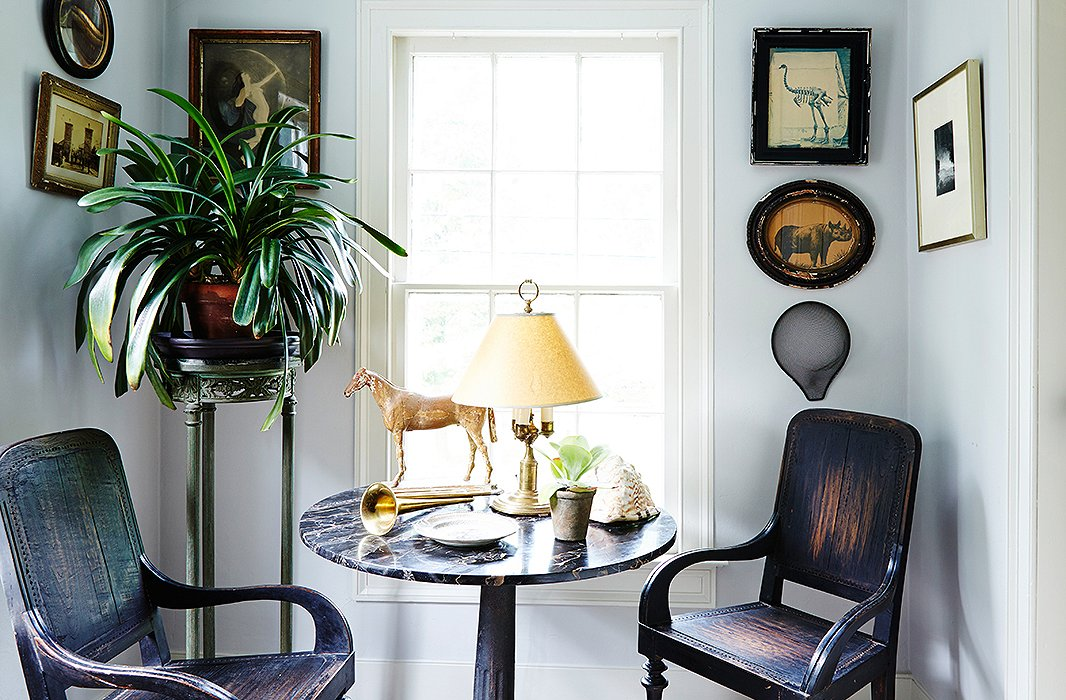 Dutch Colonial chairs from South Africa, an antique marble-top table joined to a cast-iron base, and art in weathered frames share a handsome patina.