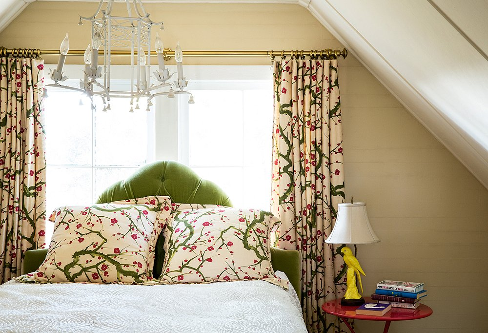 "Step into the guest bedroom and the first thing that will catch your eye is the Clarence House fabric adorning the pillows, the bed skirt, and the curtains. ""Symmetry feels very calm to me,"" says Chloe. ""It feels formal in a way that I enjoy."""