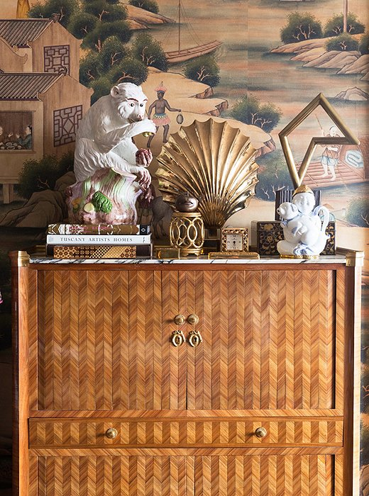 An inlaid-wood secretary, found in a New Orleans auction, shows off a curated vignette in radiant, golden hues. The hand-painted wallpaper is a custom creation by Gracie.