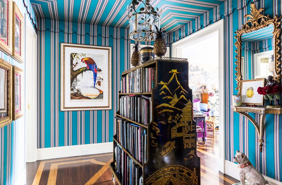 """I thought that the colors were so wonderful and whimsical,"" Alex says of the striped Lee Jofa fabric in the entryway. He found the double-sided bookcase while antiquing in Hudson, NY. ""There's nothing I like more than books."""