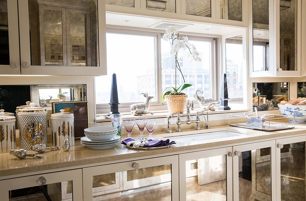 "Panels of antique mirror make the kitchen sparkle. ""I wanted my kitchen to feel like a big bar,"" Alex says."