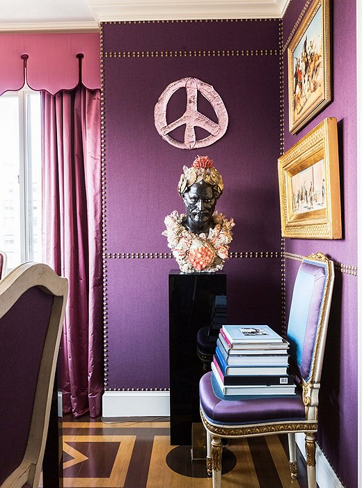 Nail-head trim imitates paneling on the dining room walls. Alex had the shell-covered bust created after an antique spotted in Paris, and the glass peace sign is by favorite artist Rob Wynne.