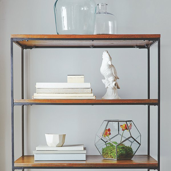 "Shelves don't always have to be crammed full of stuff—letting items ""breathe"" can help make your room feel airy and spacious."