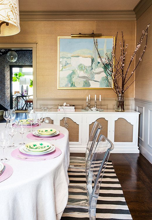 "In a dining room made formal by grasscloth walls, a vintage white sideboard, and a painting by Roger Mühl, Lucite chairs are a welcome breath of modern whimsy. ""They were affordable and wipeable,"" says Chloe. ""Sometimes at the end of a project when you have small kids, bulletproof is all that matters."""