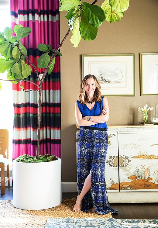 Under a fiddle-leaf-fig canopy, Chloe leans back against a chinoiserie cabinet she inherited from her grandmother.