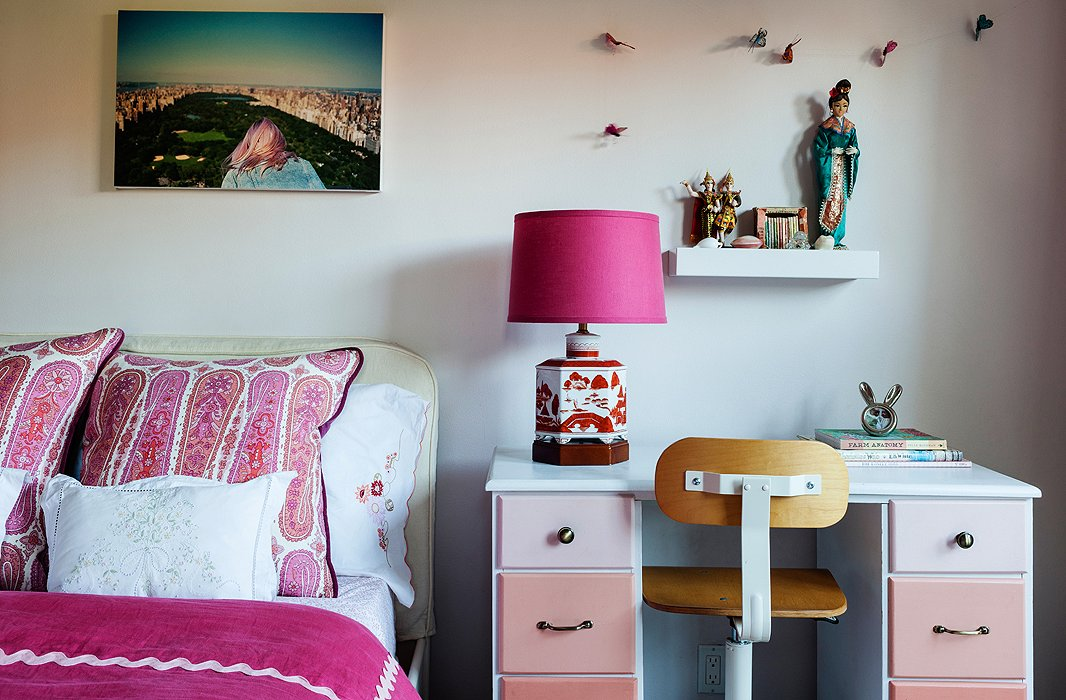 Millie's room is a sophisticated take on a typical little girl's pink paradise. Christine had the fuchsia duvet made with thick cotton rickrack and accented it with paisley pillows, a lampshade of the same material topping a chic chinoiserie lamp, and an ombré desk from Etsy.
