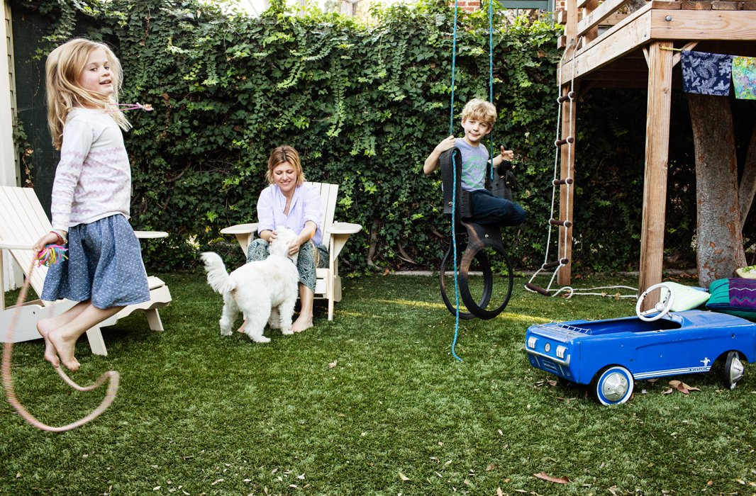 "The family's unofficial motto: Get outside. They're often in the backyard hanging with Ollie, their Wheaten-mix terrier, and swinging on the horse tire swing that was a gift from the grandparents. ""One of my favorite parts of this house are all the mature trees,"" says Christine. ""They provide so much shade and keep the house and yard 10 degrees cooler—crucial for L.A."""