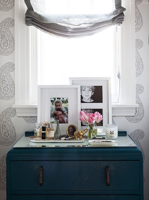 "Christine's ""me space"" is her dressing area, wallpapered with GP & J Baker wallpaper. The dresser, a Rose Bowl find, is topped with vintage trays, old family photos, and sweet little found objets her kids have gifted her."