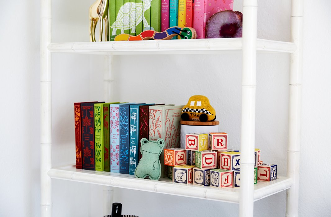 Colorful design classics share shelf space with a set of stacked blocks, brilliantly stored away while doubling as visual appeal.