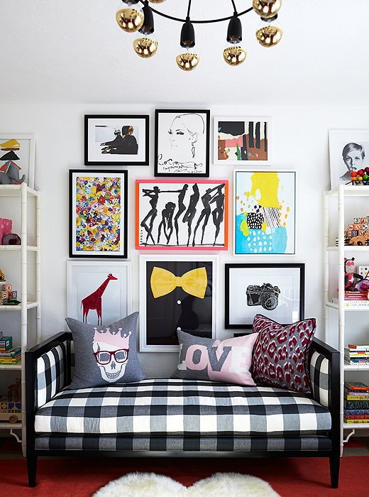 The room has a playful symmetry, centered on a black-and-white gingham daybed and a graphic gallery wall.