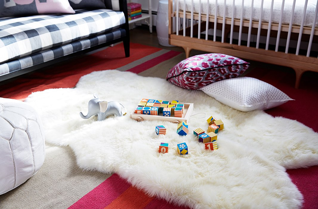 To create a soft, warm feeling, a Mongolian sheepskin, perfect for a bit of tummy time, was layered on top of a burnt-orange-and-fuchsia dhurrie.