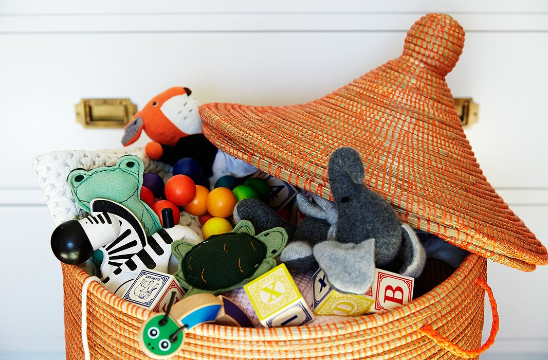 A lidded basket is an ideal spot to keep toys. Once they're mobile, children can easily get into the basket themselves, and you can quickly declutter a room by tossing all toys and blocks back in the basket.