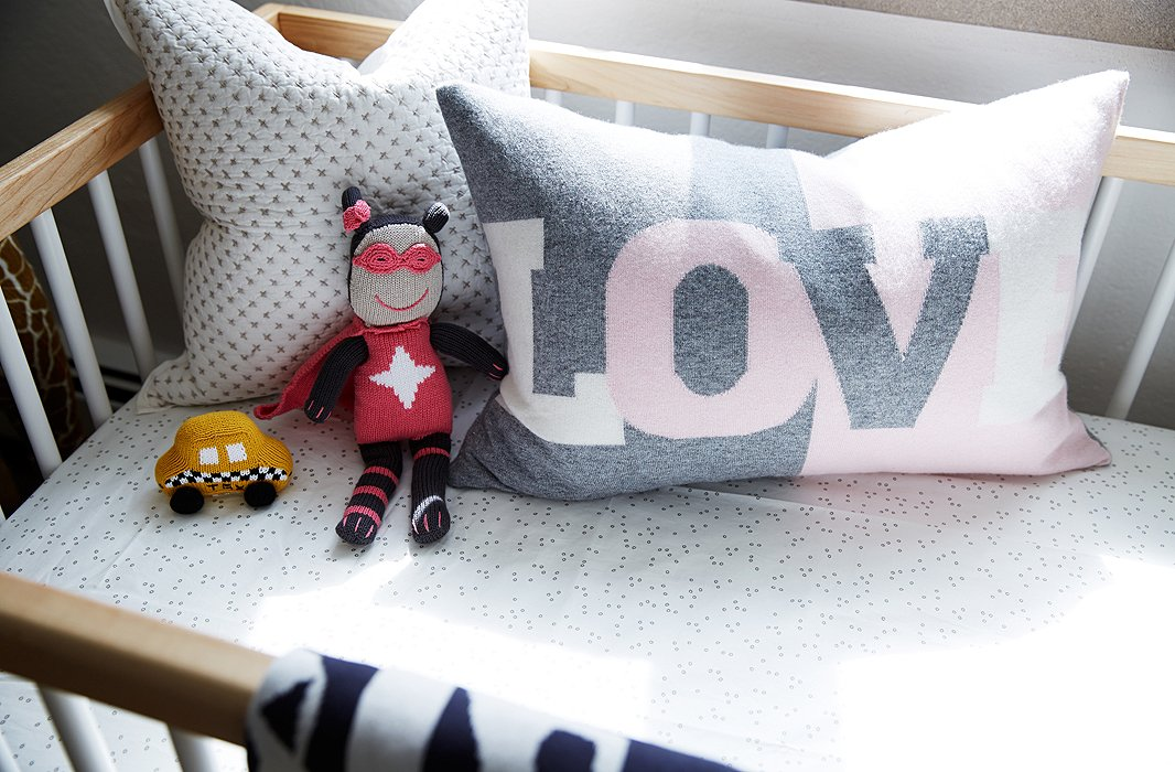 "A gray-and-pink graphic pillow picks up on the Pop art in the rest of the house. As for the toys, Coco says she ""doesn't want to get into gender rules so much. I don't think that cars are only for the boys!"""