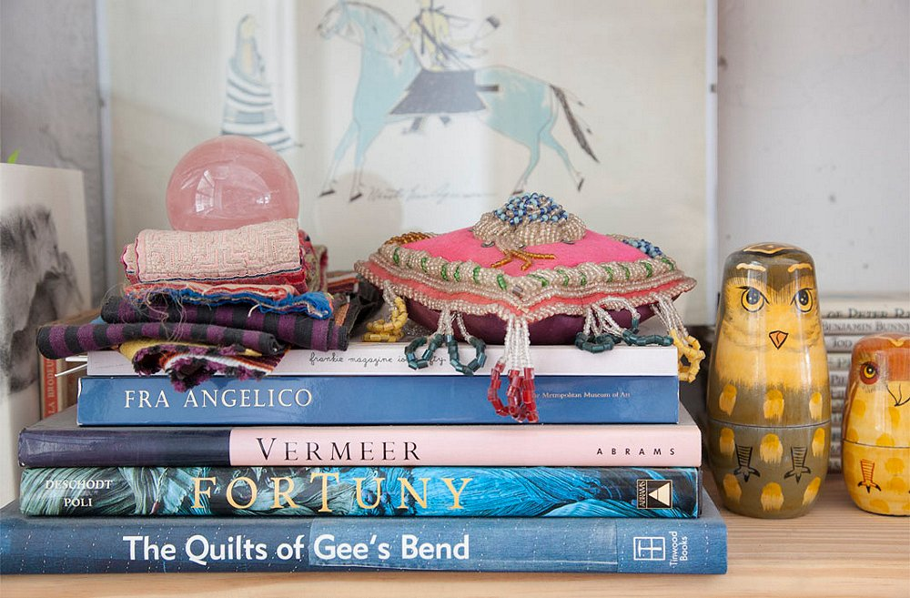 A Native American pincushion and a stack of fabric scraps (one of Housley's many collections) top a few of her favorite coffee table books. And the owls? A set of nesting dolls from a friend.