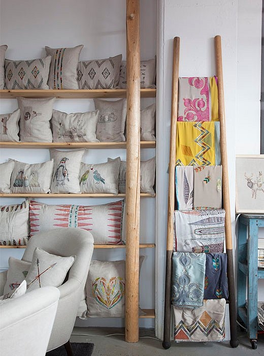 Embroidered linens and pillows hang out on built-in shelves made from horse-rail fencing by carpenter Tim Miller.