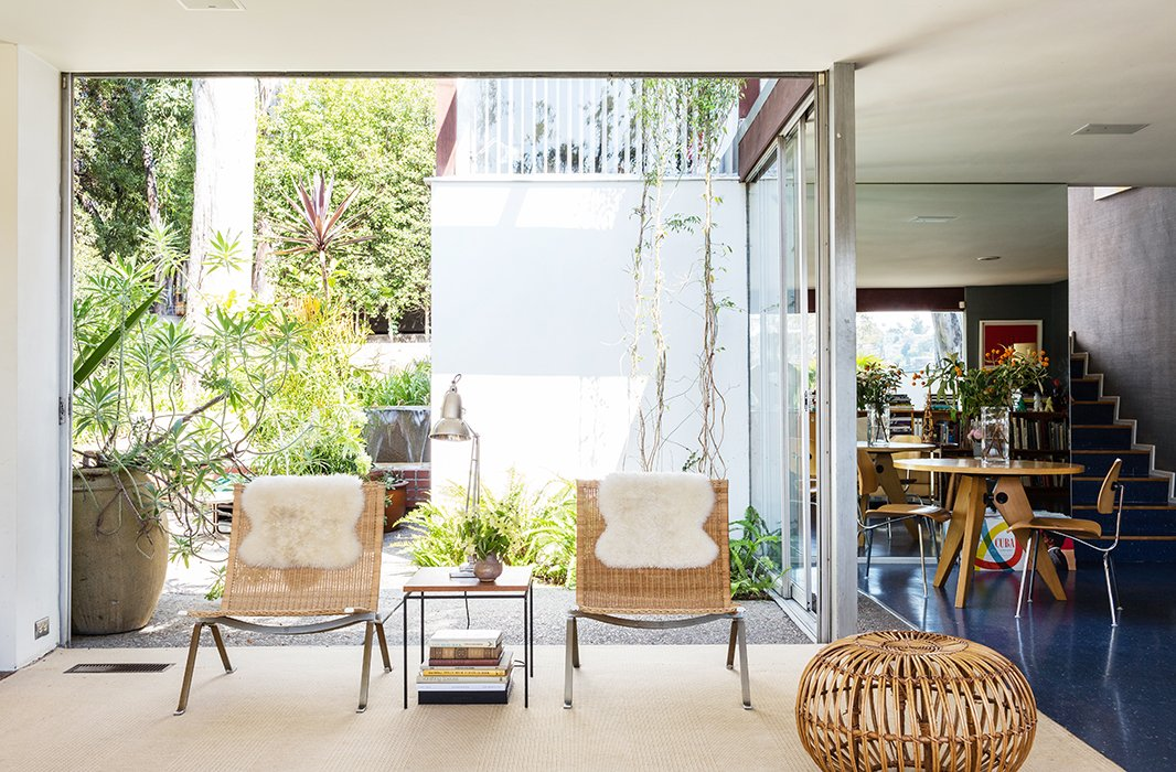 Natural elements (and nature) help ease up the sleek lines of the glass-encased home, playing up the great California promise of living outdoors. The PK22 chairs, by Poul Kjaerholm from Wyeth, and a neutral carpet keep open the view into the interior courtyard.