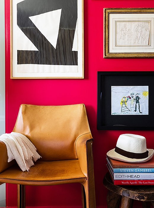 A bold red wall in the master bedroom features a range of favorite art pieces, from a 1970s gouache by Al Held to a 17th-century drawing from David's parents to a drawing by one of his daughters that was an anniversary gift.